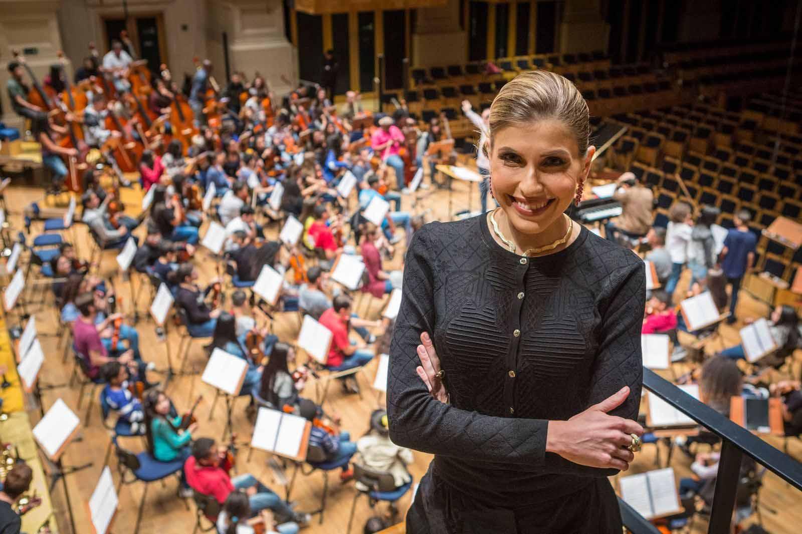 pianista sorrindo fundo orquestra crianças