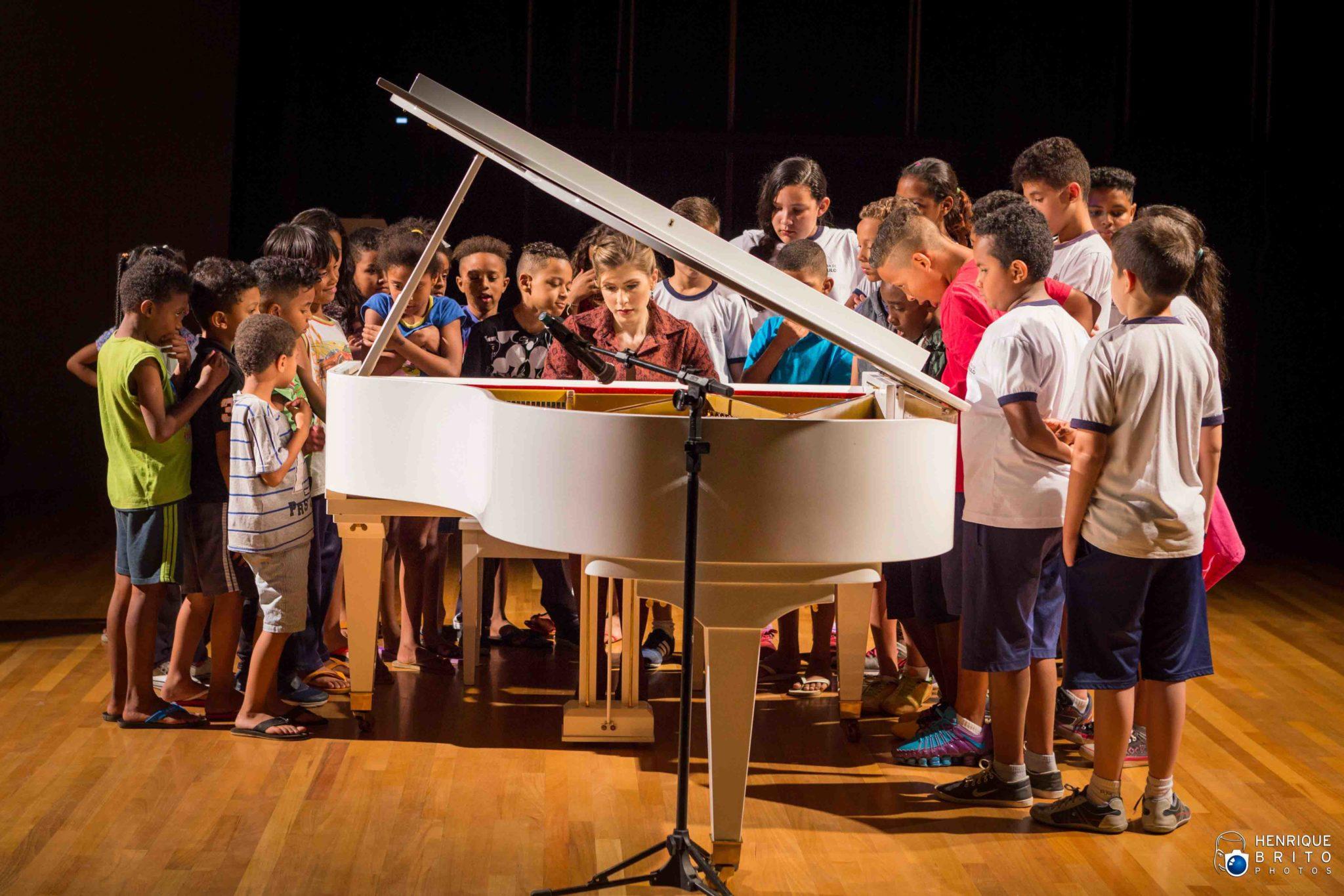 pianista toca piano cercada crianças palco