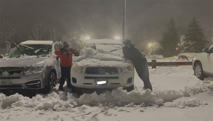 Criança e jovem limpando neve em carro para ajudar enfermeiras que trabalham na linha de frente do combate à covid-19