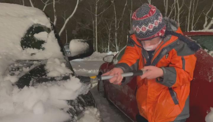 Criança limpando neve de carro