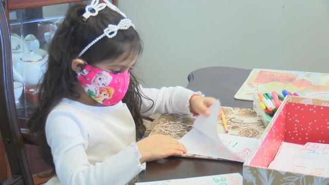 Menina desenhando em mesa com lápis de cor