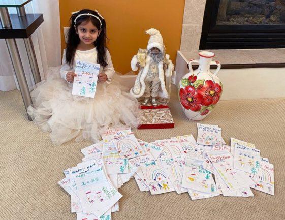 Menina sentada ao lado de boneco do Papai Noel e vaso e centenas de cartões desenhados