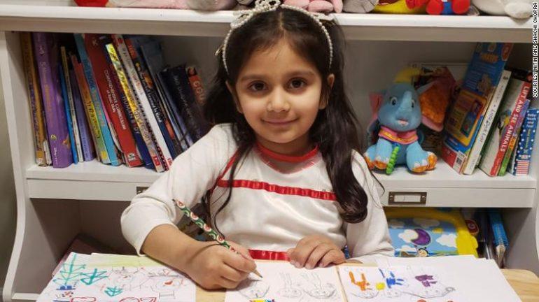 Menina desenhando em mesa com lápis de cor e sorrindo