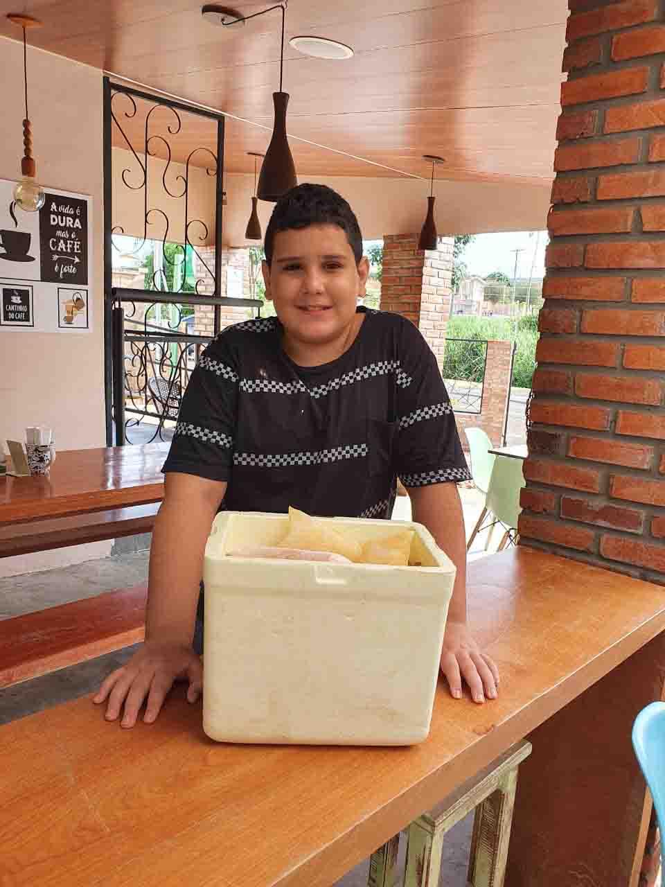 menino sorrindo com caixa de geladinho em cima bancada