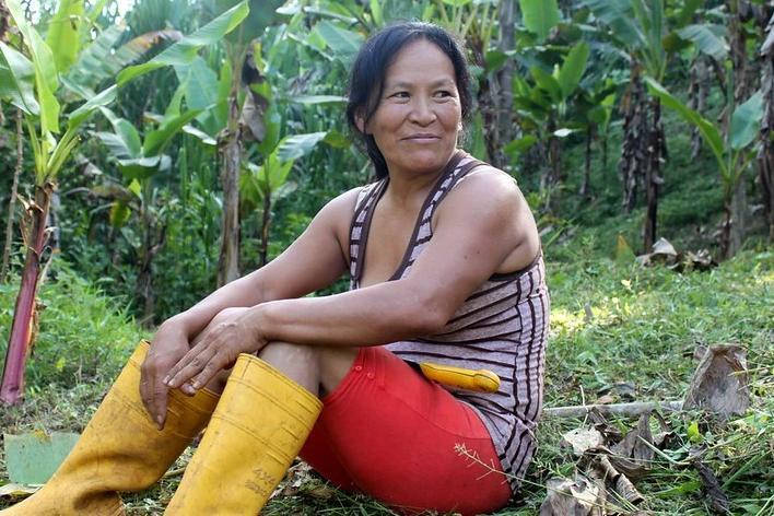 mulher indígena sorrindo sentada segurando ferramenta plantio árvore
