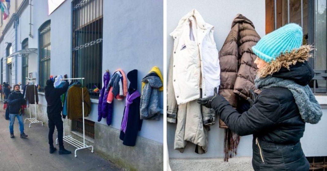 Homem agasalhado pendurando roupa em muro
