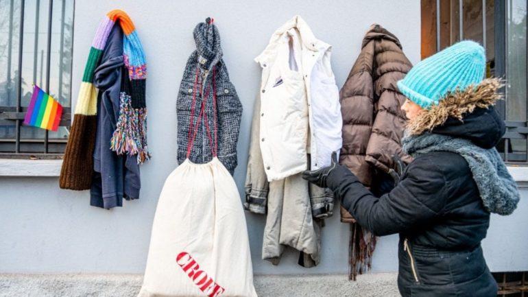 Mulher agasalhado pendurando roupa em muro