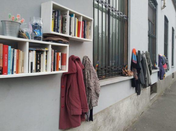 Muro com livros e roupas de doações pendurados