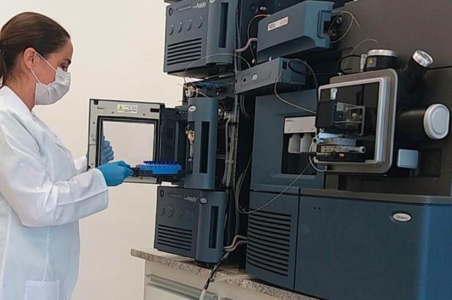 Mulher de jaleco avaliando sangue em máquina de pesquisa
