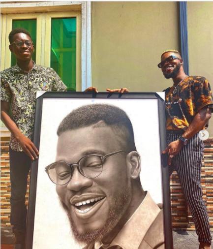 Dois homens segurando quadro com pintura realista de um rosto