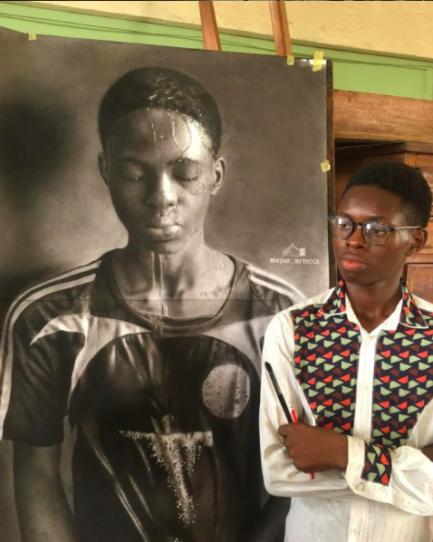 Jovem pintor nigeriano de braços cruzados em frente ao seu autorretrato