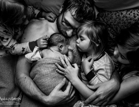 Homem abraçado com filho recém-nascido e rodeado por três filhas maiores