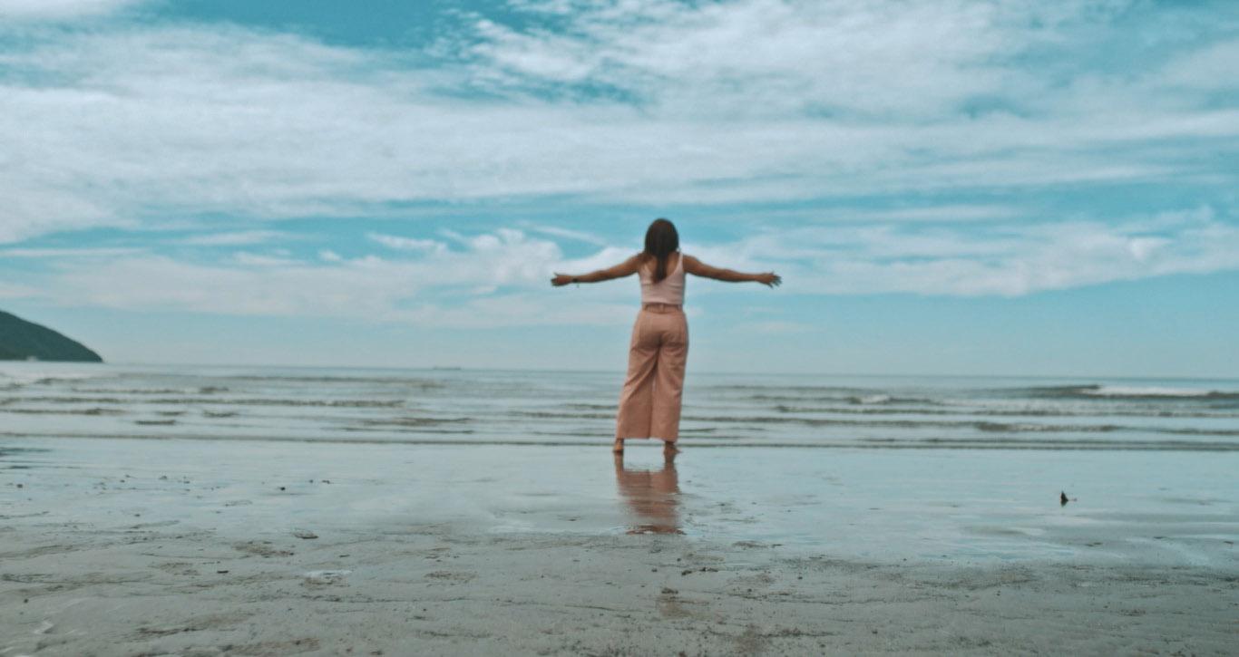 mulher braços abertos areia praia frente mar