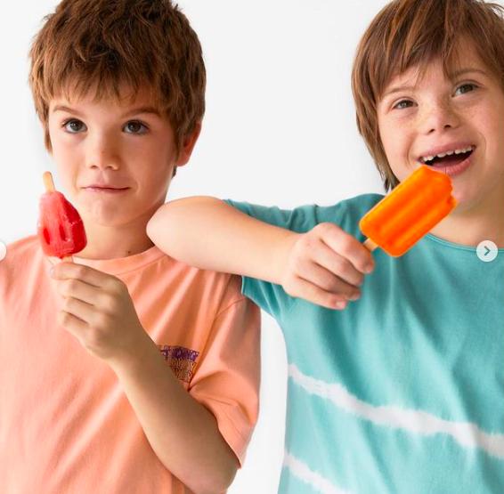 Duas crianças, uma delas com síndrome de down, tomando picolé