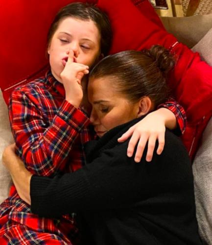 Filho com síndrome de down abraçando a mãe que está dormindo
