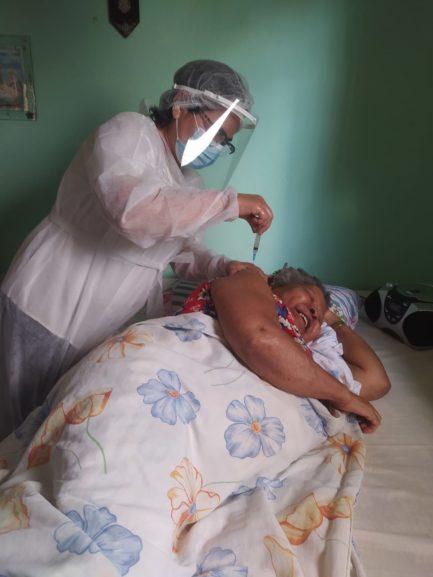 Idosa sorrindo ao ser vacinada em cama