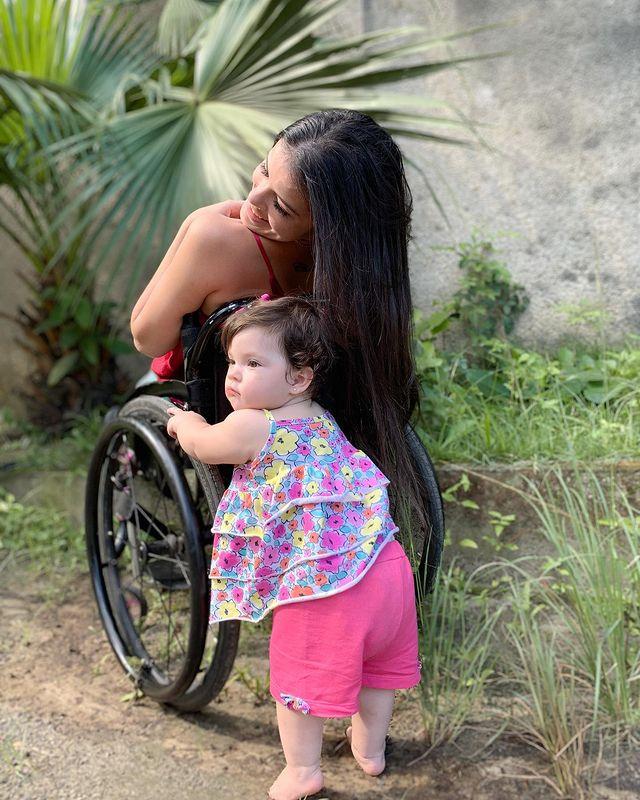 filha de um ano ajuda mãe paraplégica a colocar seus pés na cama