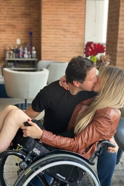 mulher beija marido sentada cadeira de rodas
