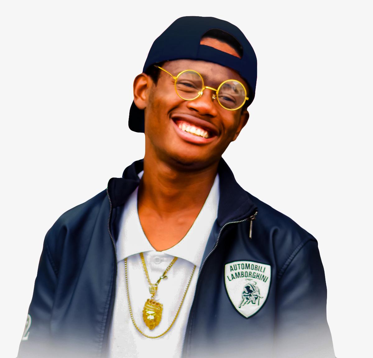 O jovem Tomray, que realizou seu sonho de se tornar rapper graças à ONG Fábrica dos Sonhos; na foto, garoto usa boné pra trás, óculos e sorri