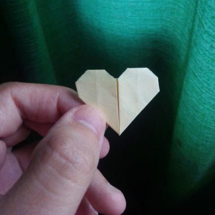 Mão segurando origami de coração