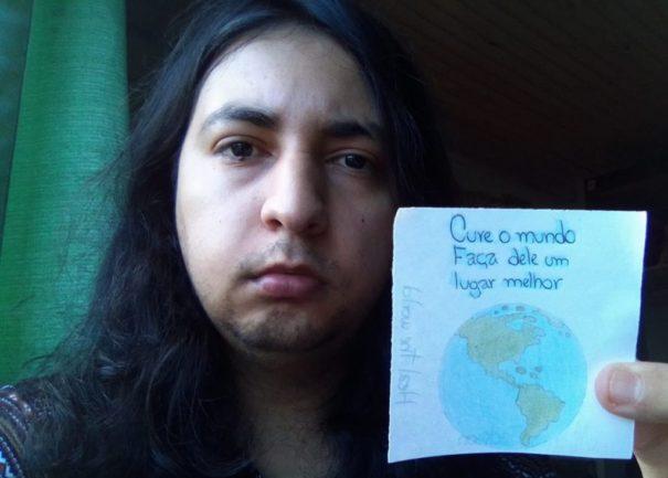 Homem de cabelos longos com papel com mensagem motivacional e desenho do mapa do mundo