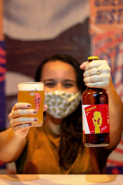 Mulher segurando garrafa e copo de cerveja