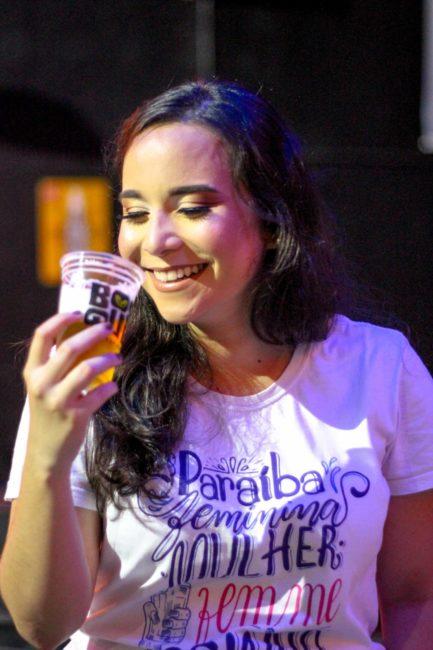 Mulher sorrindo tomando cerveja