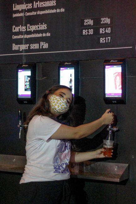 Mulher tirando cerveja de máquina de chopp