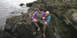pai e filho sentados rocha ilha