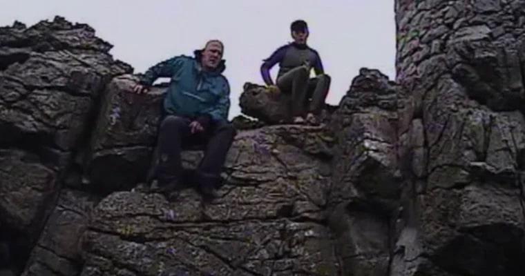 pai e filha sobre rocha em ilha