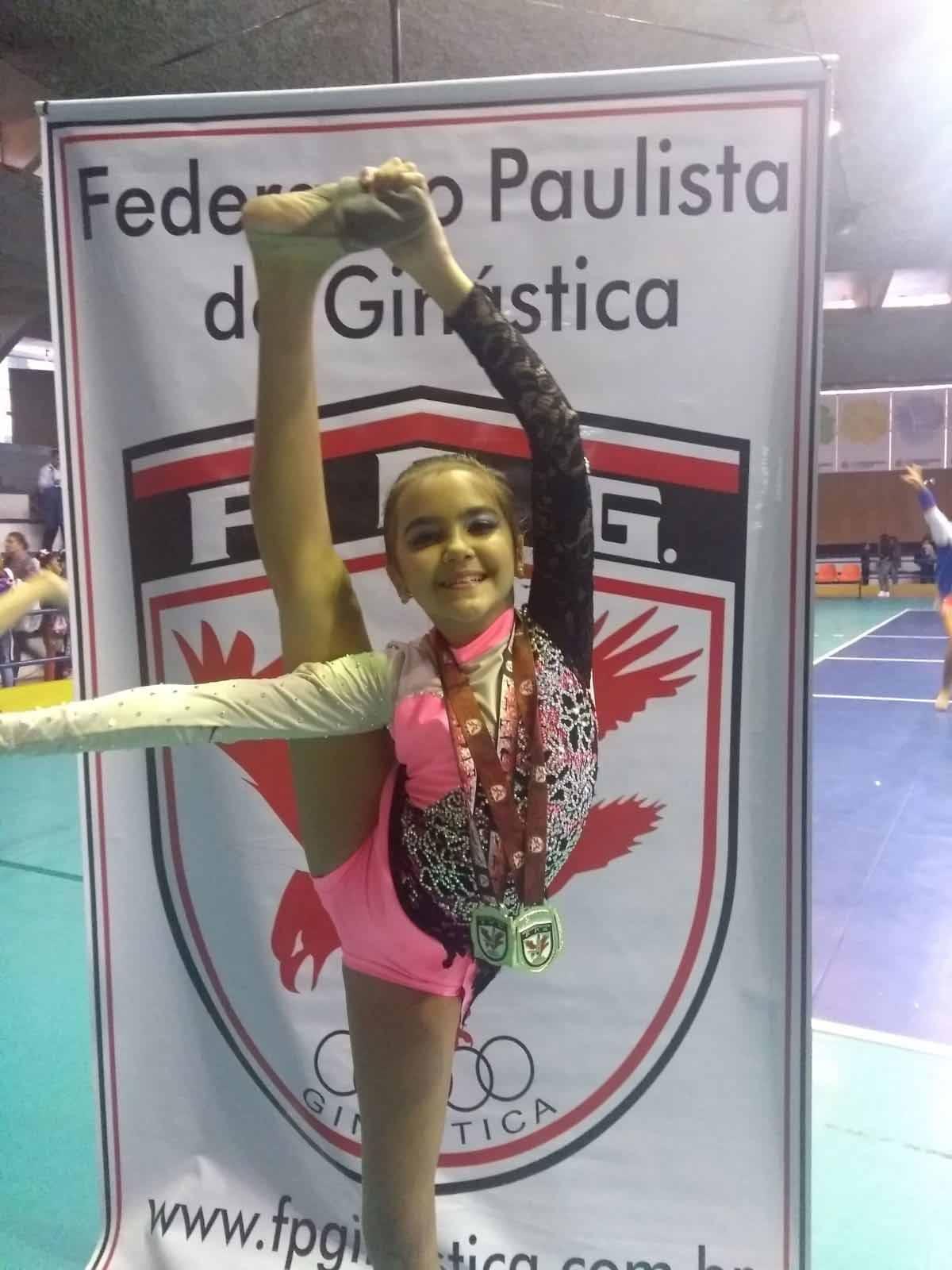 Ginasta Lavínia com medalha que ganhou na Federação Paulista de Ginástica