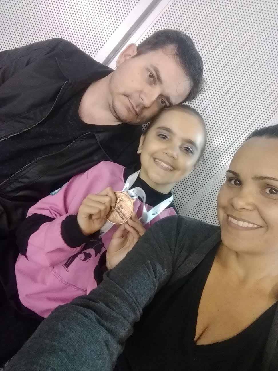 Ginasta Lavínia com seus pais enquanto segura medalha