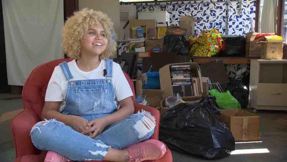 menina poltrona biblioteca comunitária sorrindo