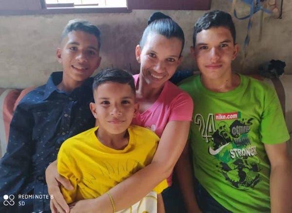 Samuel, menino com asperger, e sua família. Na foto, mulher com seus 3 filhos sentados em sofá