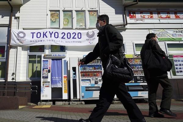 Mulher mais velha do mundo carregará tocha olímpica. Na foto, japoneses andam nas ruas do país de máscaras