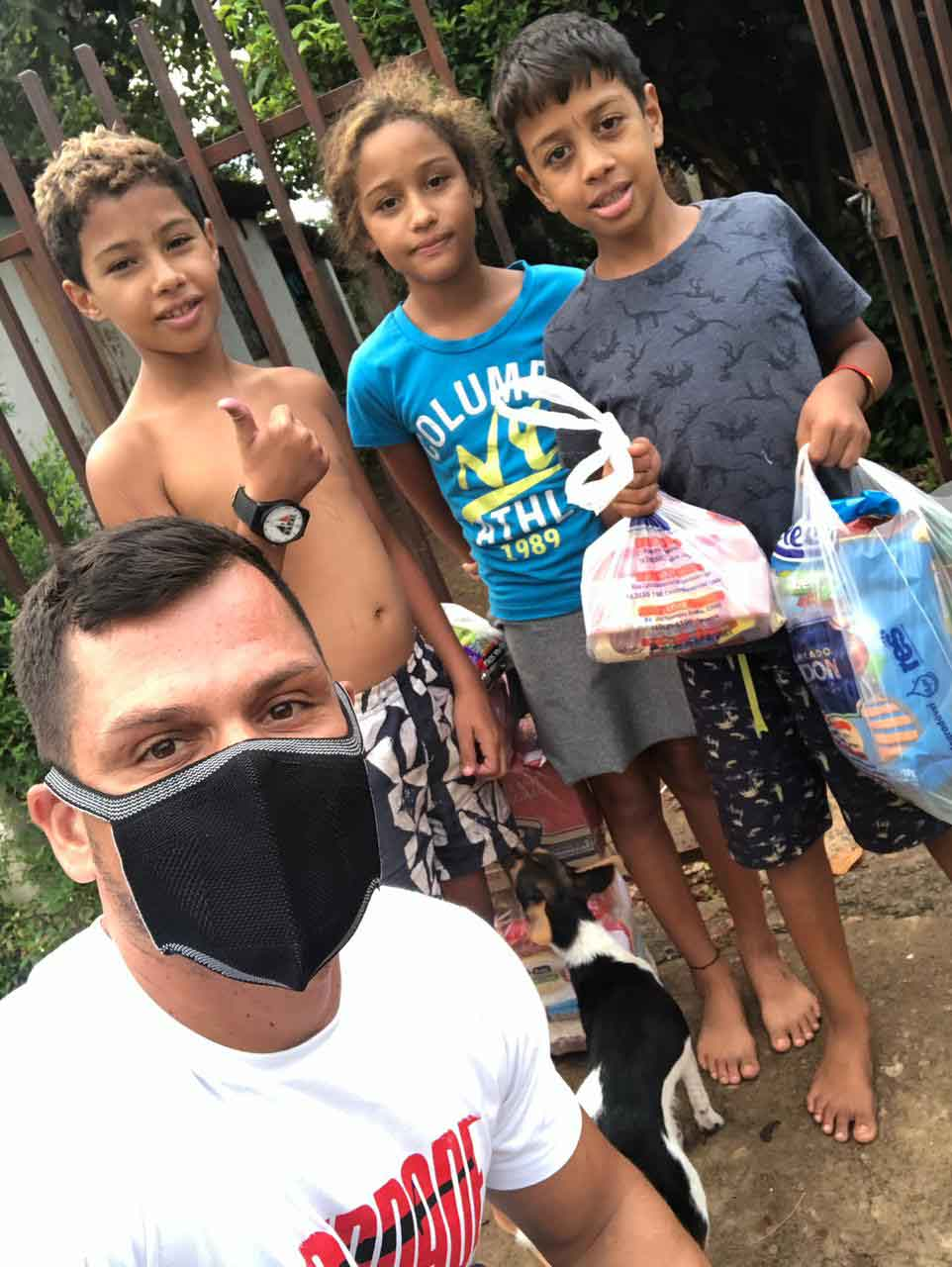 selfie sargento com crianças segurando doações alimentos