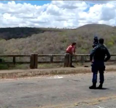 Mulher em ponte com dois policiais próximos