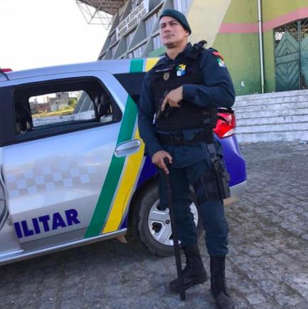 Policial com fardamento, arma e na frente da viatura