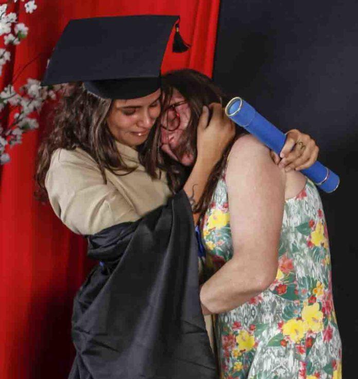 filha usa uniforme de faxineira da mãe em formatura; na foto, filha abraça a mãe