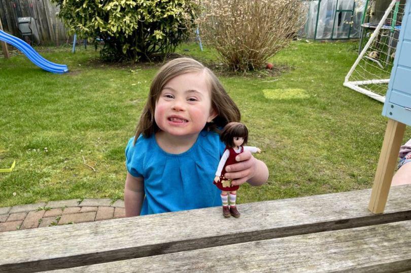 menina com síndrome de down sorrindo com boneca