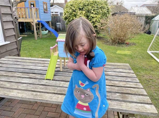menina com síndrome de down abraçando boneca com mesmas características