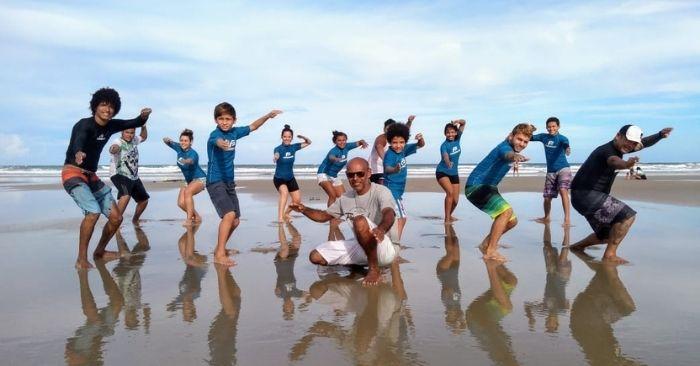 Professor de surf com alunos na praia