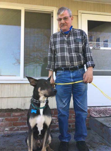 tutor idoso ao lado cão frente casa