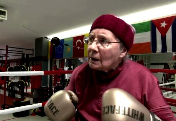 Senhora Nancy que luta boxe para diminuir os sintomas do Parkinson. Na foto, ela de luvas de boxes e touca enquanto luta