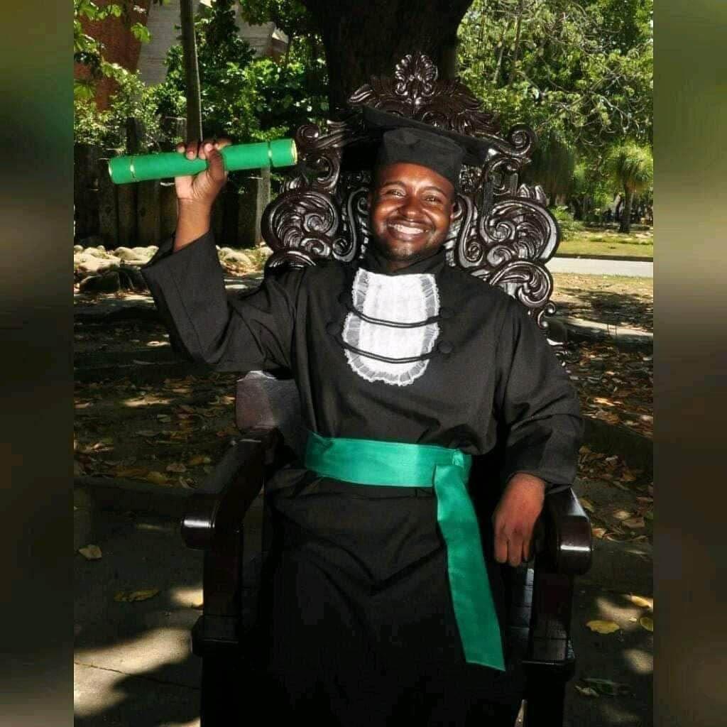 jovem vestindo beca formatura faculdade segurando diploma