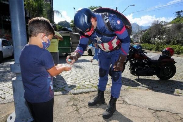 homem fantasiado de Capitão América aplicando álcool em mão de menino