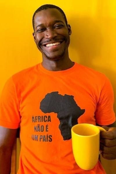 Africano posa foto sorrindo segurando caneca
