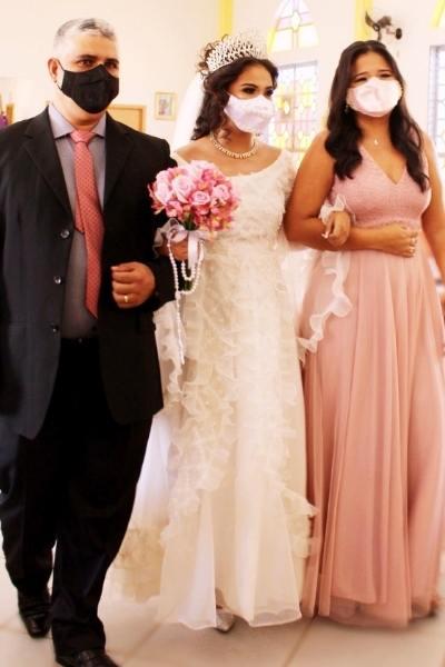 noiva entra na igreja de braços dados com pais