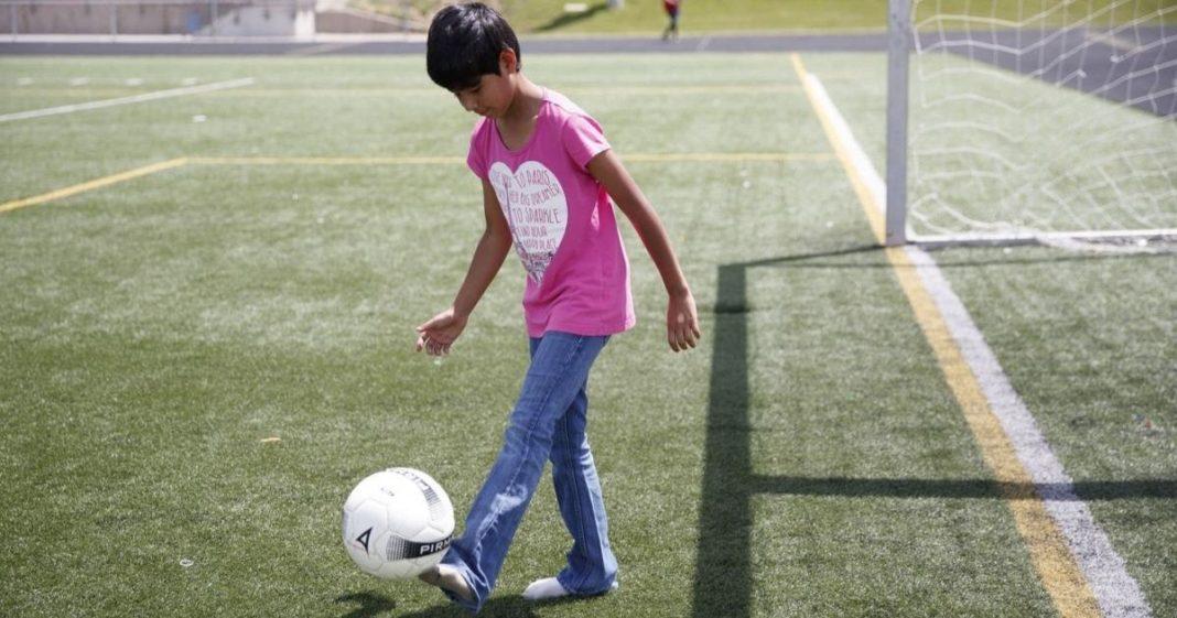 menina cabelo curto em capo com bola no pé