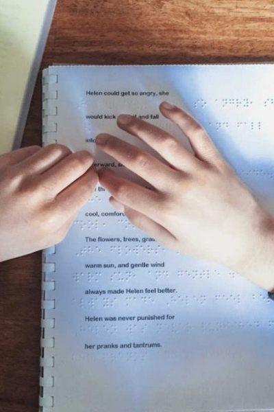 mãos sobre livro em braille